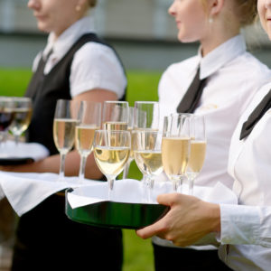 Waitress with dish of champagne and wine glasses